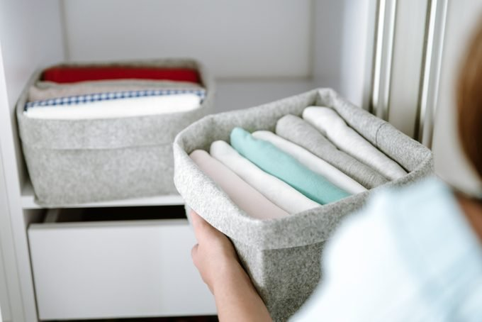 Woman organizing clothes in wardrobe, putting shirts in boxes, baskets into shelves. Clothes neatly folded after laundry. Concept of minimalist lifestyle