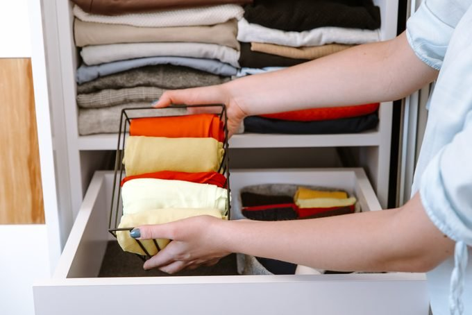 Woman organizing clothes in her closet, putting shirts in boxes and baskets into shelves and drawers.