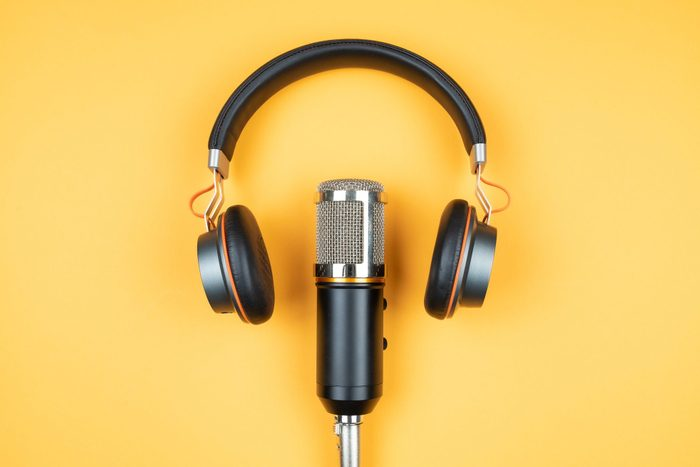 directly above view of headphones and podcast microphone on orange background