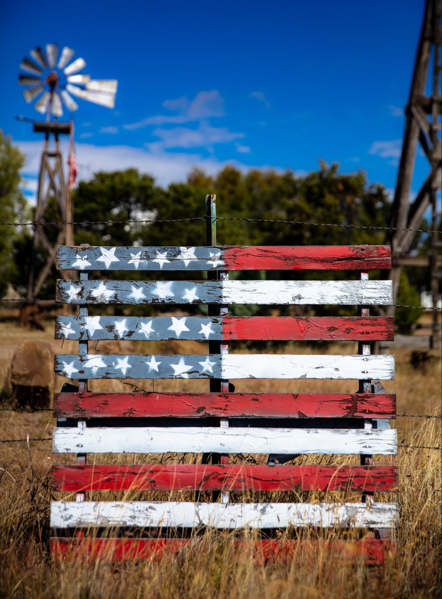 An old fashioned windpump against a bright blue sky behind a wooden pallet painted with the stars and stripes of the american flag