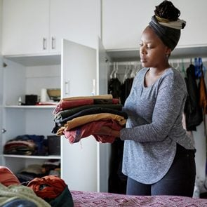 woman organizing the clothes from her bedroom closet at home