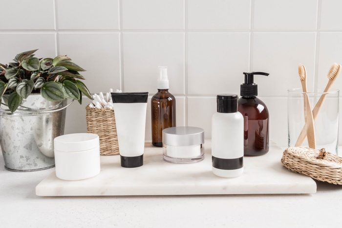 White bath background with cosmetic bottles