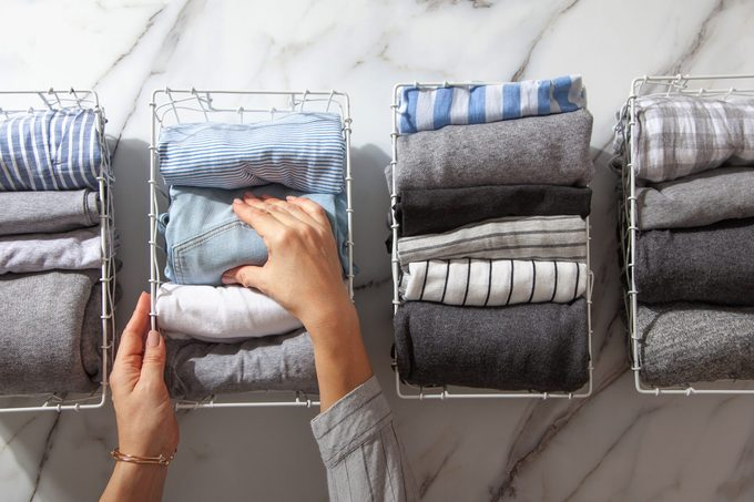 hands organizing folded clothes in wire baskets