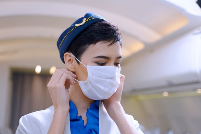 Air hostess is demonstrating for wear protective face mask.