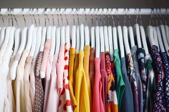 clothing in a closet organized by color from light to dark