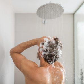 Man taking a shower washing hair under water falling from rain showerhead in luxury walk-in bath. Showering young person at home lifestyle. Body care morning routine in sunlight