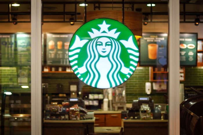 starbucks logo on exterior of glass with out of focus interior in the background inside