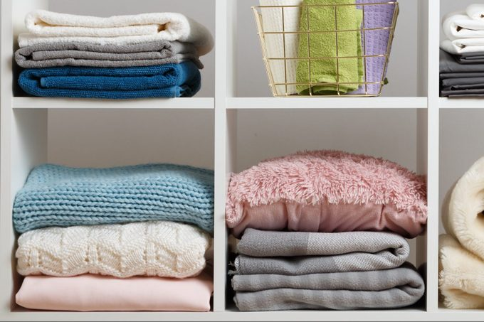 Stacks of towels, sheets, bedding, clothes, blanket and pillow on a white shelf.