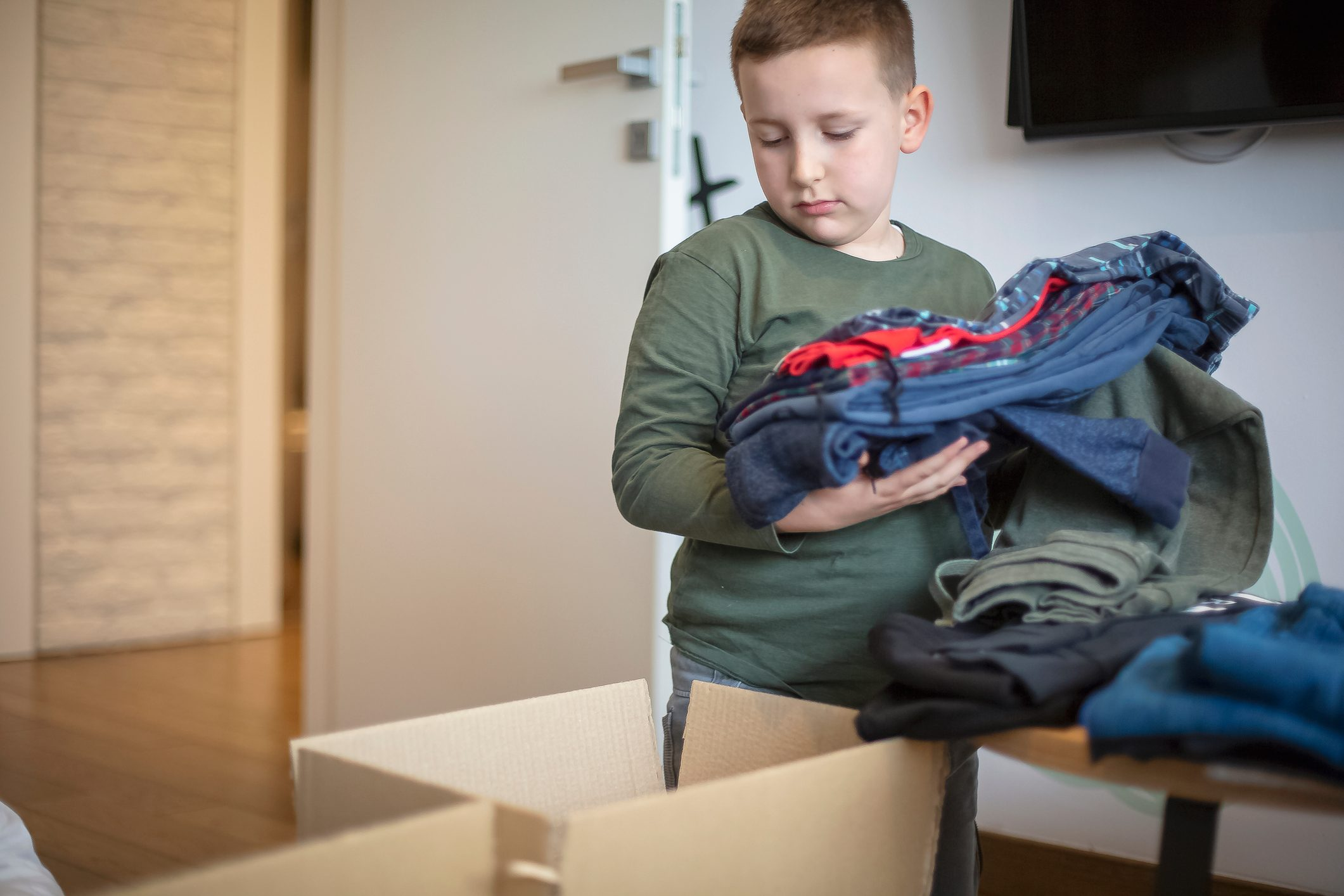 Children sorting clothes from their closet for donation