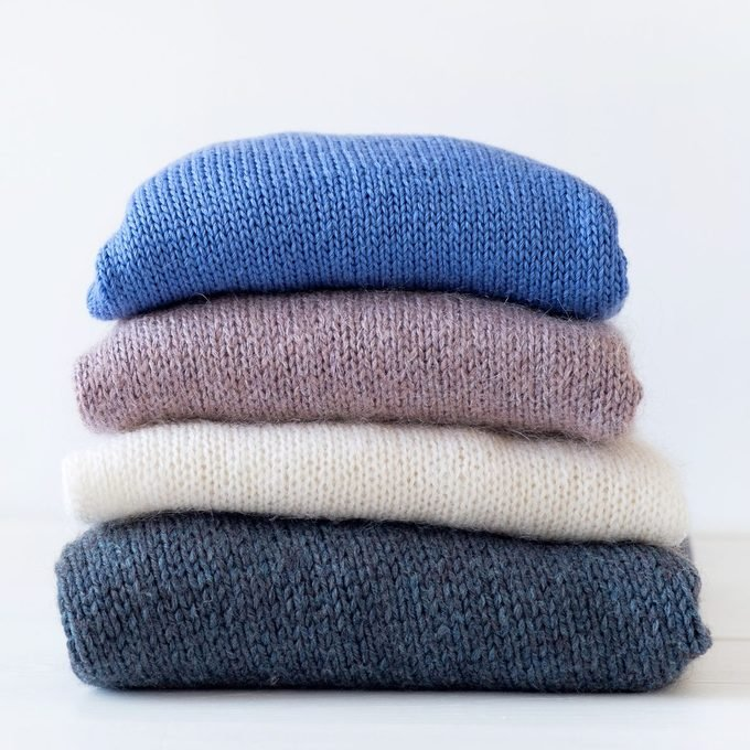 Knitted Woolen Things Of Different Colors, Stacked In A Pile, Lie On A White Wooden Table. Winter And Autumn Warm Cozy Sweaters For Charity. The Concept Of Storage, Care And Washing Of Handmade Products. Copy Of The Text Space.