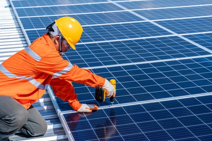Asian technicians using an electric drill installing solar cells to produce and distribute electricity. Solar energy technology concept