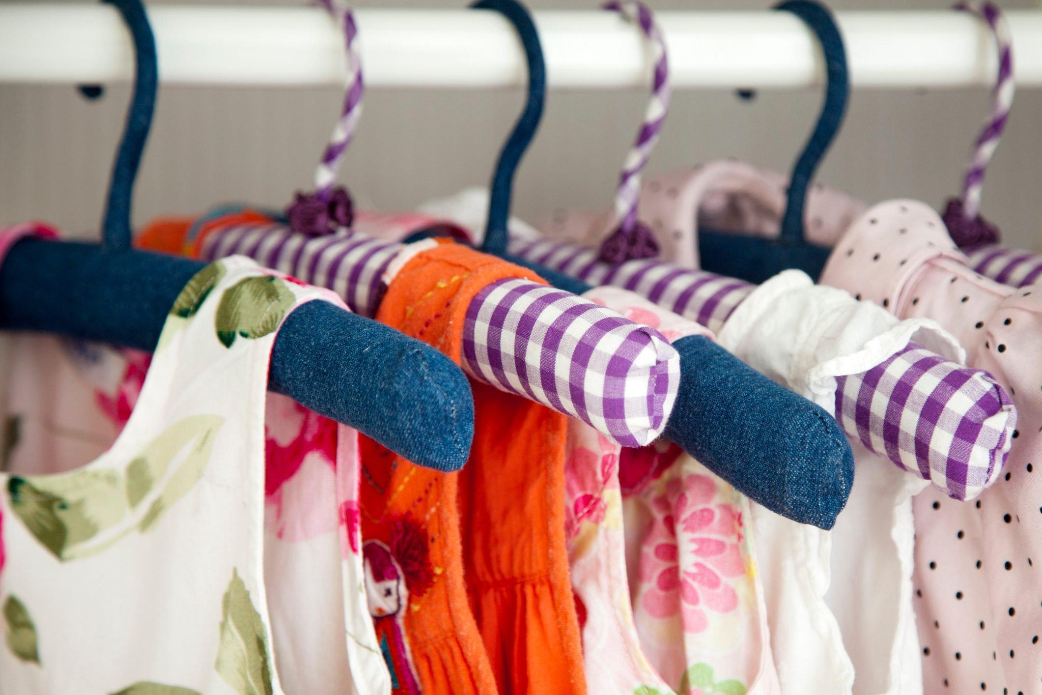 Colorful dresses hanging in wardrobe