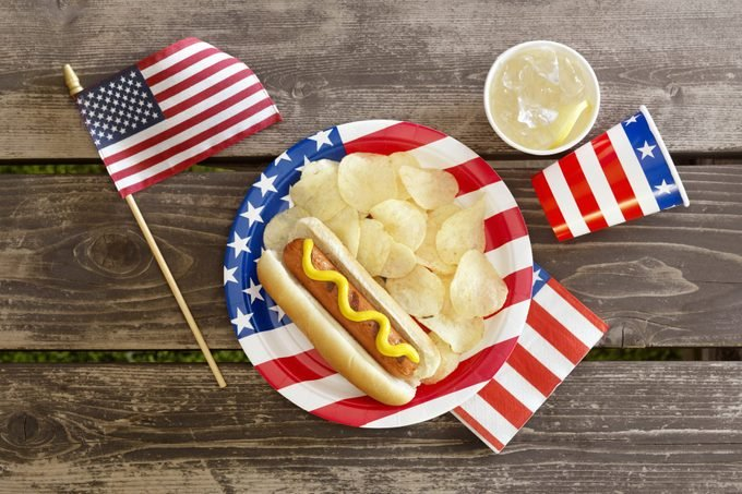 fourth of july still life: overhead view of small american flag, flag plate with hot dog and chips, and flag cups and napkin on a wood table background