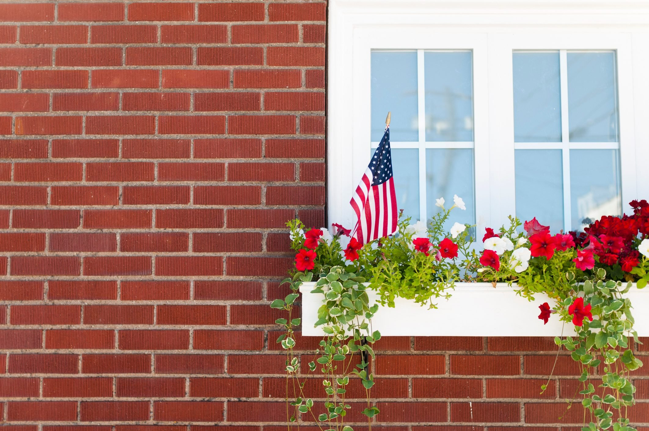 White washed window on a brick building with a flower filled window box and american flag sticking out of it.