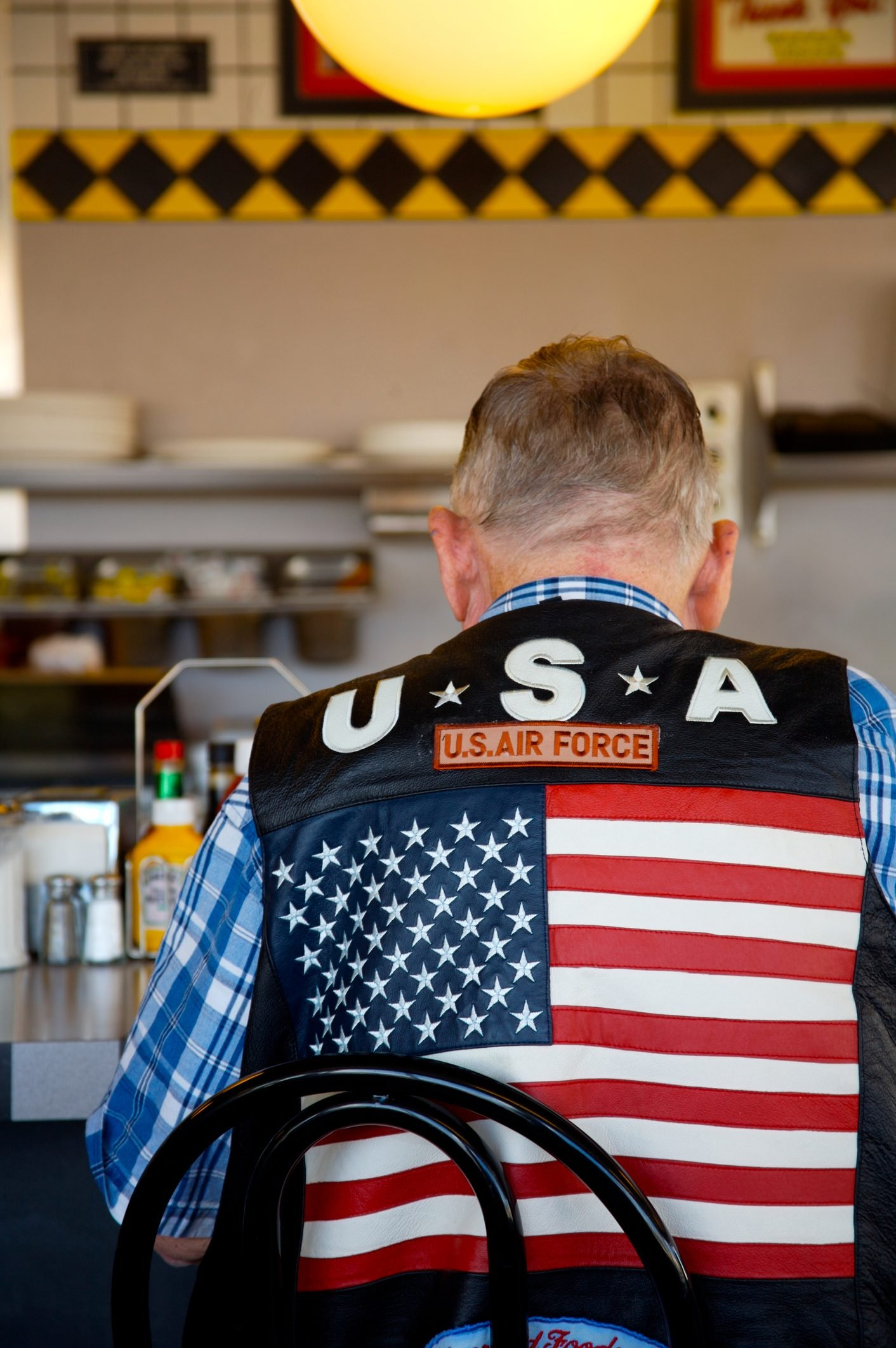 A man seated at a diner counter wearing an air force vest with a large american flag on the back.