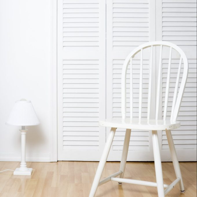 White chair and louvered closet doors