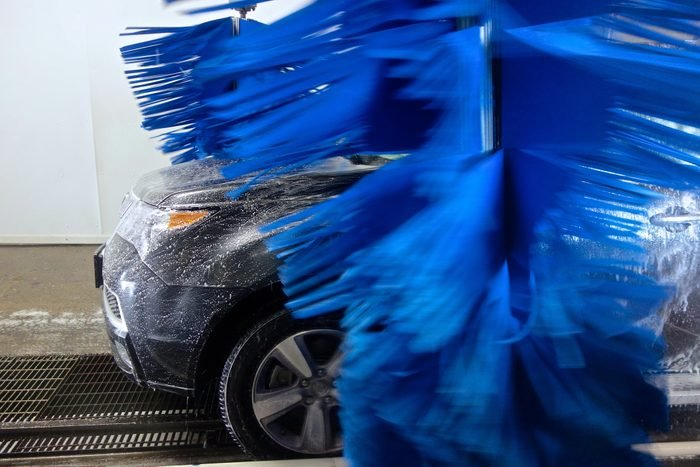 A side-profile of a soapy front-end of an SUV in an Automatic Carwash with Brushes spinning.