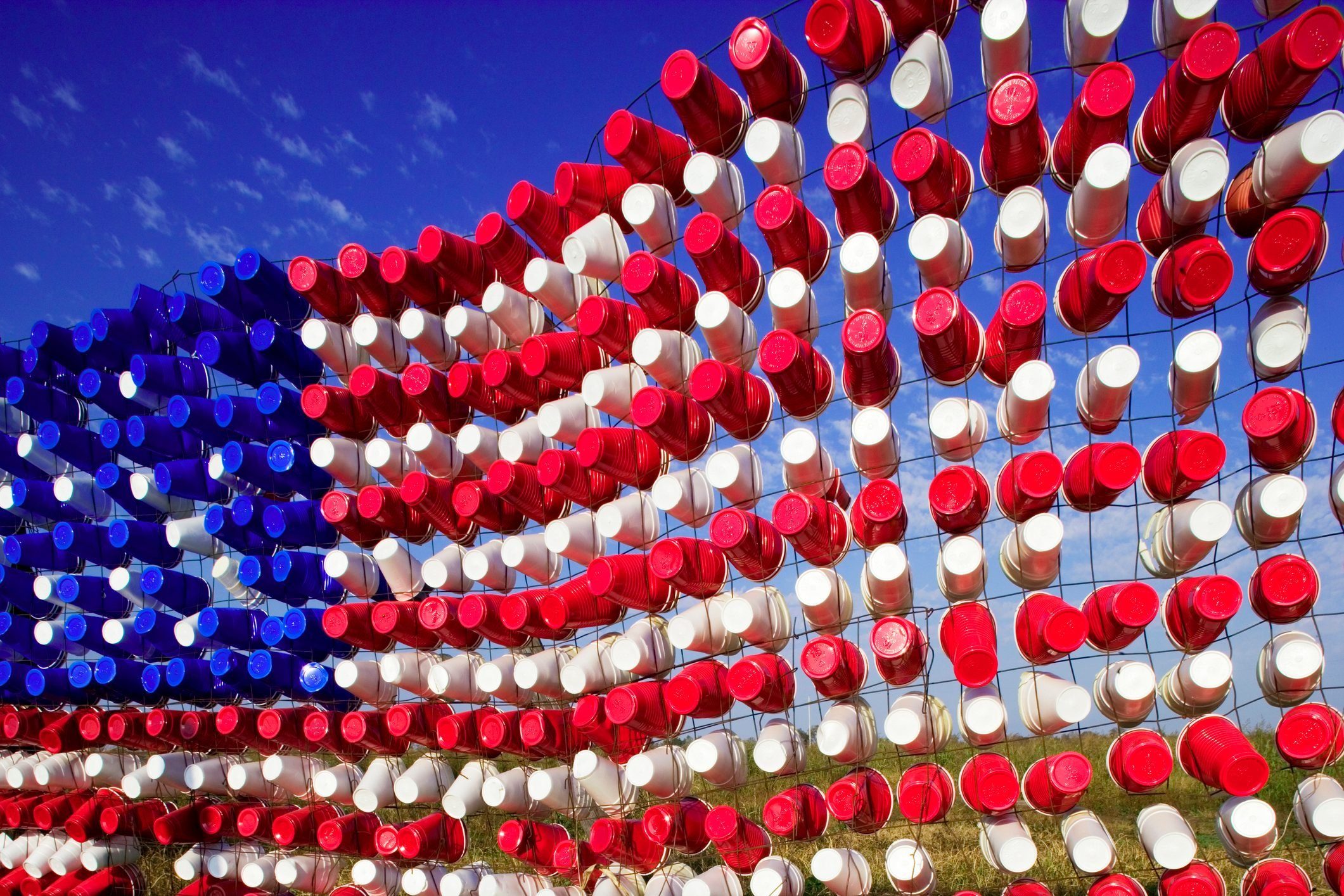 American Flag created out of empty plastic cups stuck in a fence, Leland