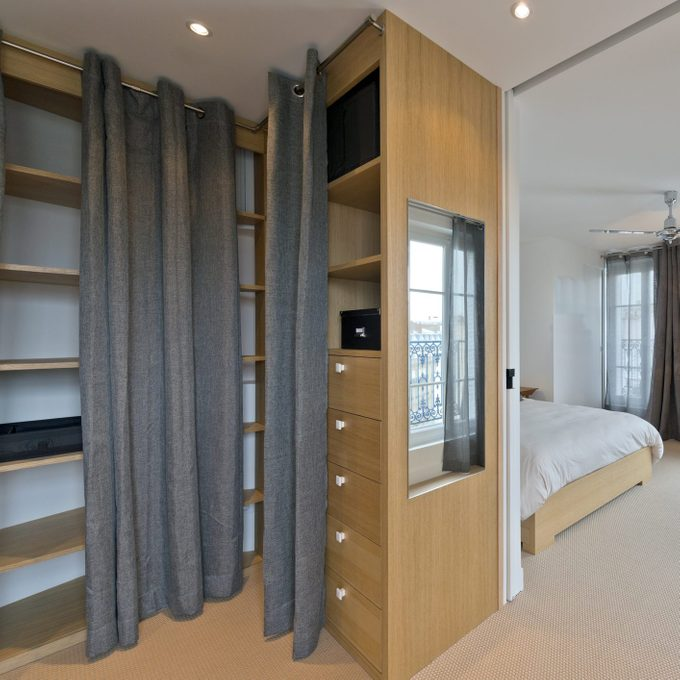 Modern bedroom interior with curtains as closet doors