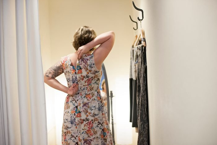 Young woman trying on dress in changing room