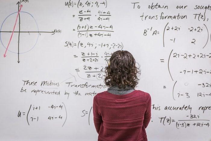 Caucasian professor examining equations on whiteboard