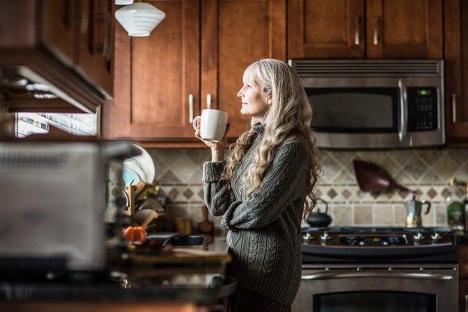 Portrait of woman (60yrs) having coffee in kitchen