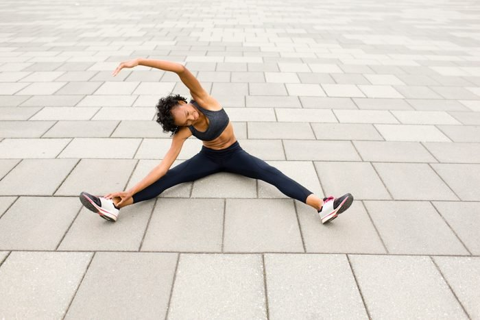Woman sitting on pavement legs apart doing stretching exercises