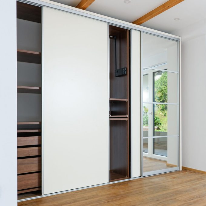 Modern bedroom closet with sliding doors, one panel is a mirror