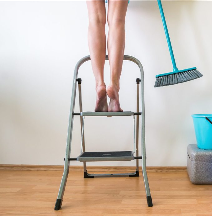 Woman Standing On Step Ladder