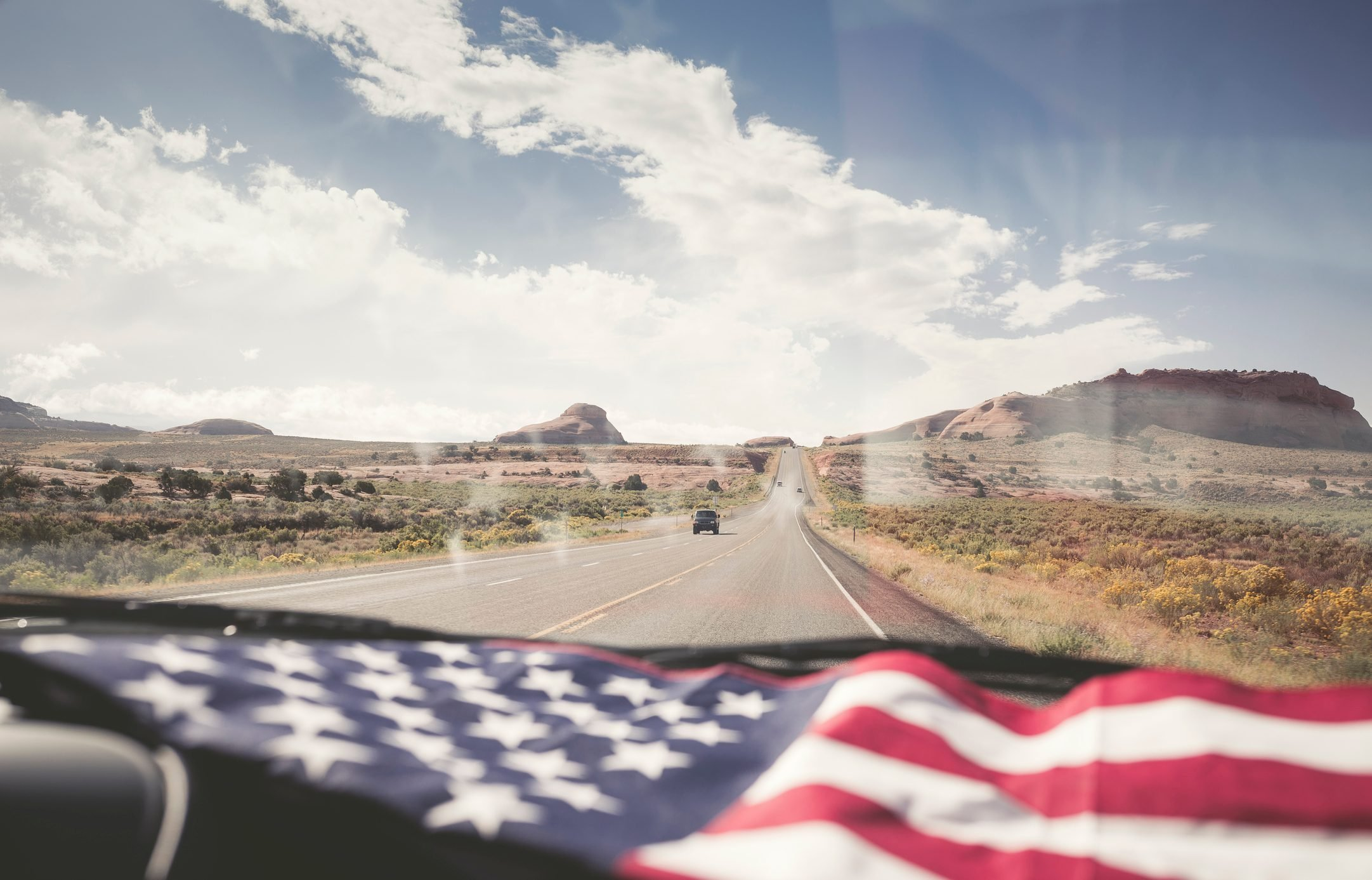 American Flag lying on dashboard of a car on the road in Utah