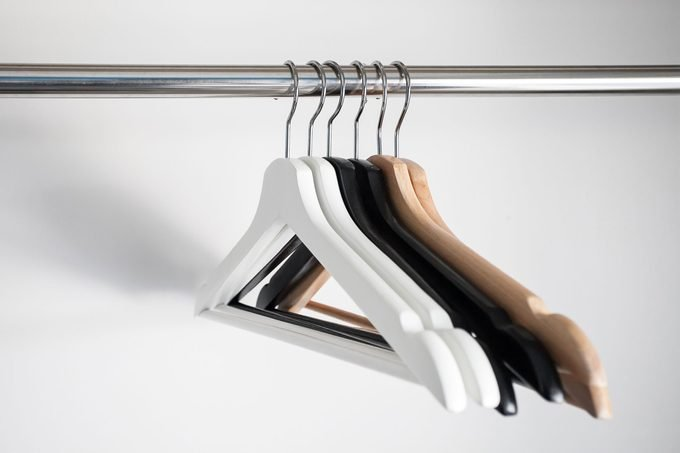 different types of hangers hanging in an empty closet