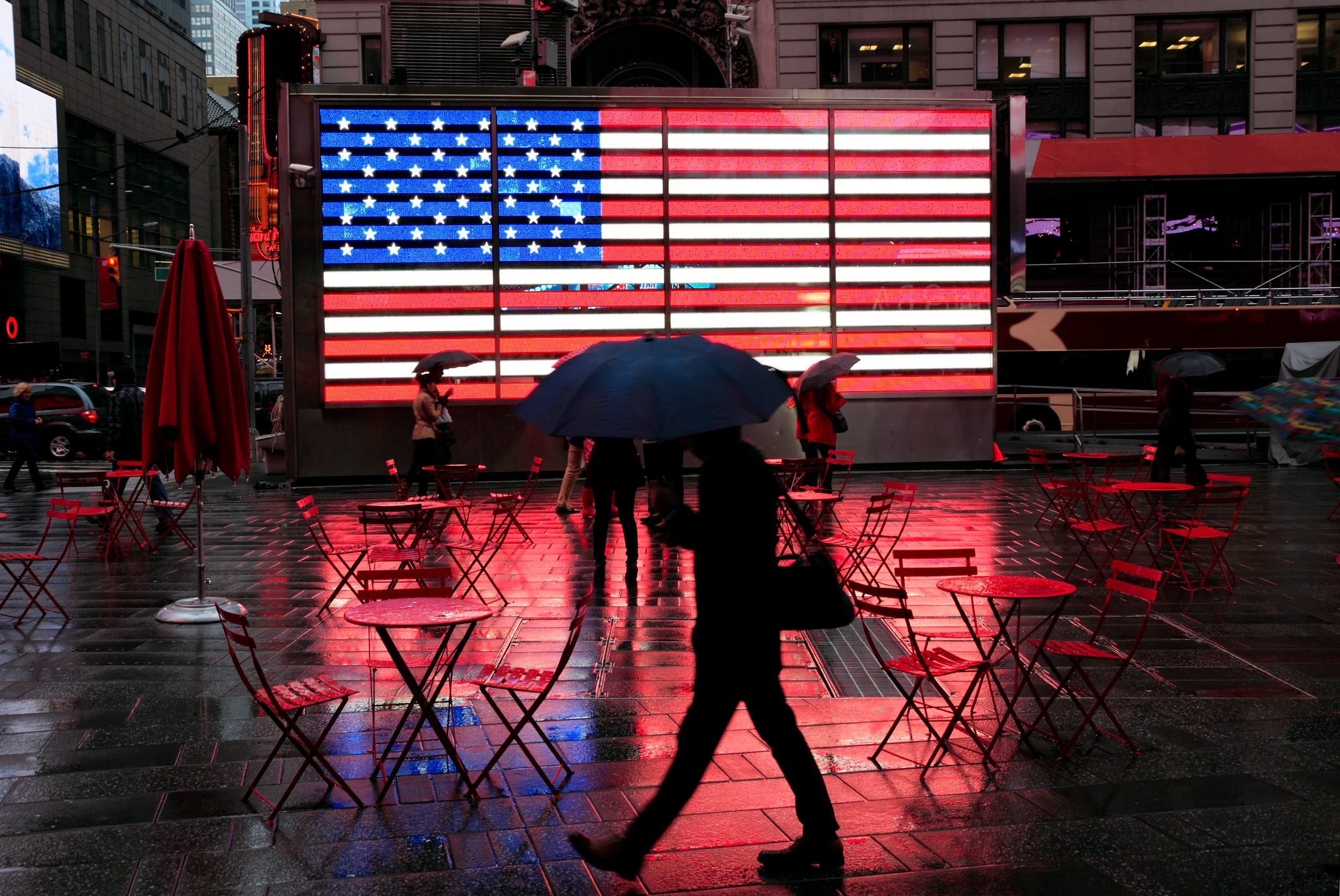 City in the Rain: silhouette of pedestrian with umbrella passing famous LED american flag in wet Times Square