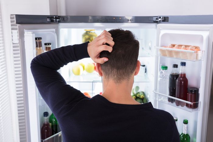 Confused Man Looking At Food In Refrigerator
