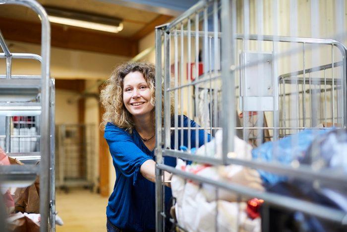 Smiling mature female volunteer pushing cart while looking away at warehouse