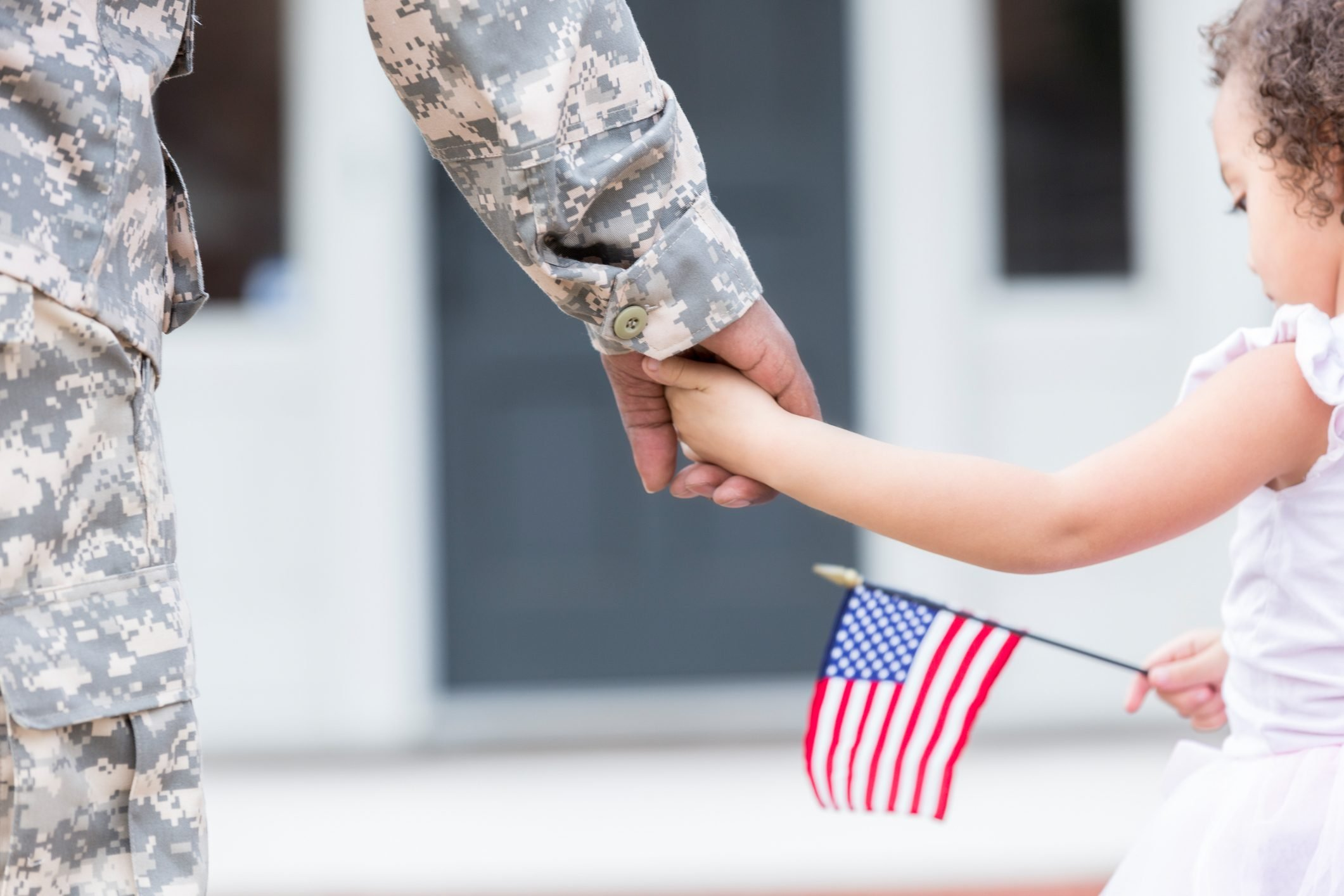 Soldier and his young daughter walk hand in hand and the daughter holds a small american flag