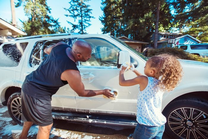 Father and daughter washing car in driveway