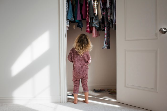 Rear view of girl standing at closet