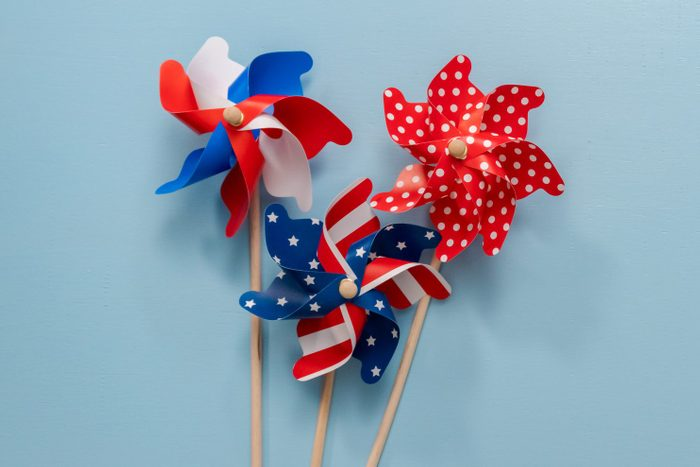 July 4th theme paper pinwheels on blue background.