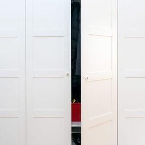 Modern white wooden closet door ajar to show organized interior