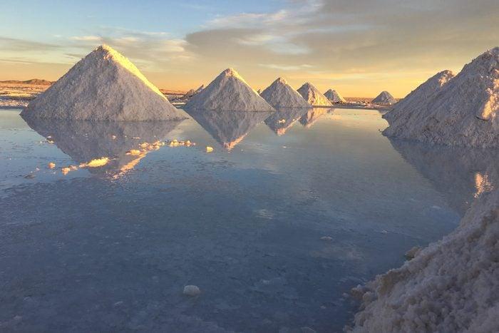 Salt By Calm Lake Against Sky At Salar De Uyuni in Bolivia