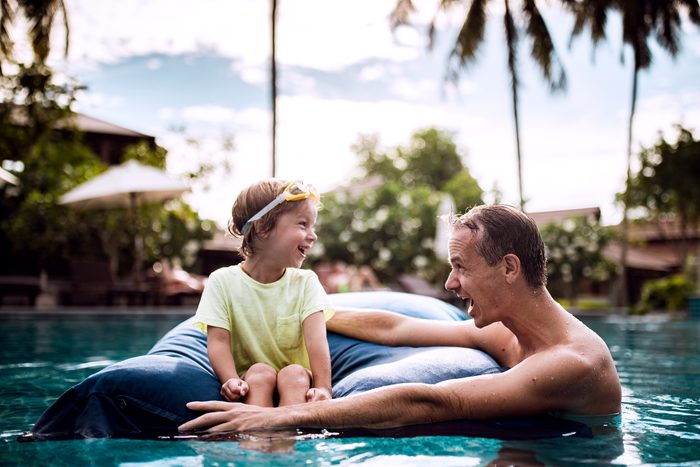father and sun hanging out in pool at resort