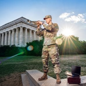 Sergeant Jacob Kohut playing trumpet in full army outfit