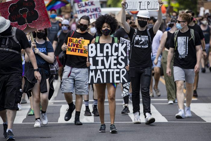 """A woman walks among a marching crowd with a """"Black Lives Matter"""" sign in washington, dc"""