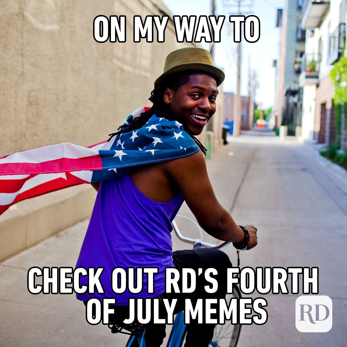 """Man wearing American flag and riding bike with meme text: """"On my way to check out RD's Fourth of July memes"""""""