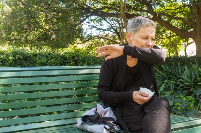 woman on bench coughing