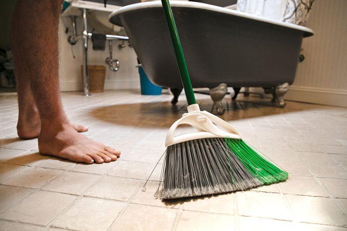 man sweeping bathroom floor before he mops it
