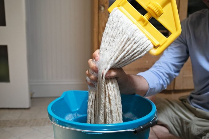man squeezing water out of mop