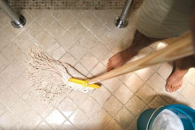 man moping bathroom floor in swishing motion