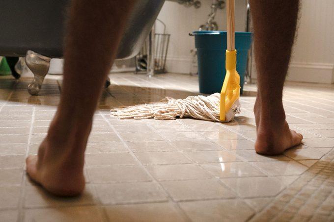 man moving backwards as he mops the bathroom floor