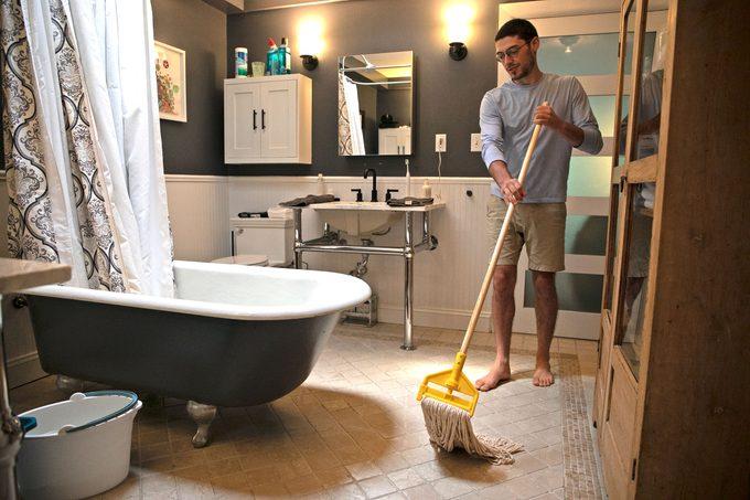 man moping bathroom floor